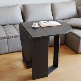Черный столик перед серым диваном