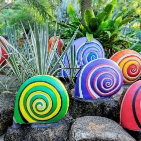 Декоративные улитки на садовой клумбе