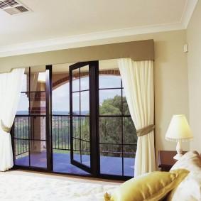 Белые шторы с подхватом на окне с балконной дверью