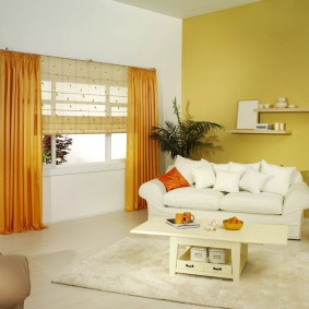Белый диван возле желтой стены