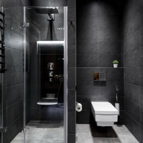 Белый унитаз в темной ванной комнате