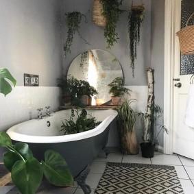 Круглое зеркало над чугунной ванной