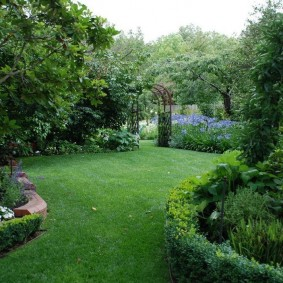 Ровная лужайка в саду пейзажного стиля
