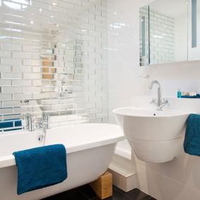 Синее полотенце на бортике белой ванной