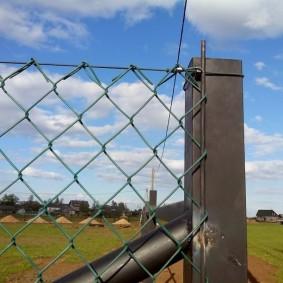 Закрепление сетки арматурой на столбе ограды