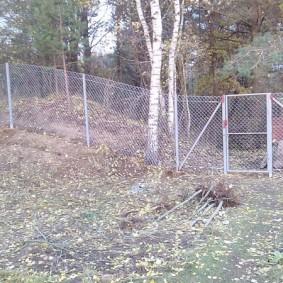 Забор из оцинкованной сетки на склоне участка