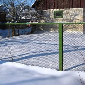 Зеленый забор из сетки зимой на даче