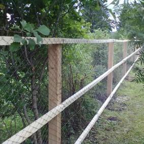 Деревянный каркас на заборе из сетки