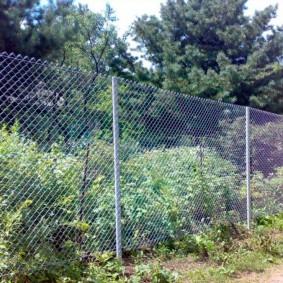 Высокая ограда из проволочной сетки