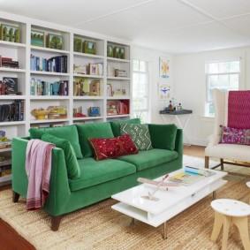 Белый стеллаж за зеленым диваном