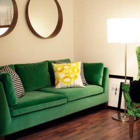 Декор зеркалами стены над зеленым диваном