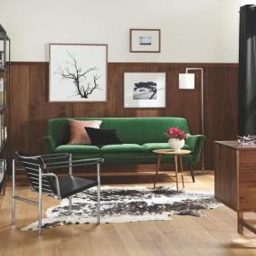 Зеленый диван в комнате с деревянной отделкой