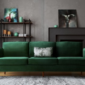 Темно-зеленый диван в комнате с серыми стенами