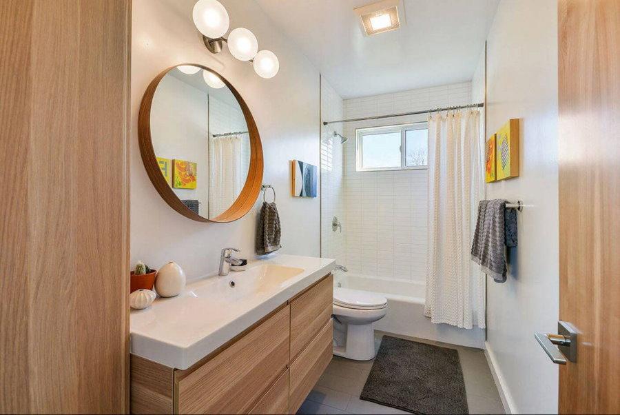 Серый коврик на полу ванной комнаты с туалетом