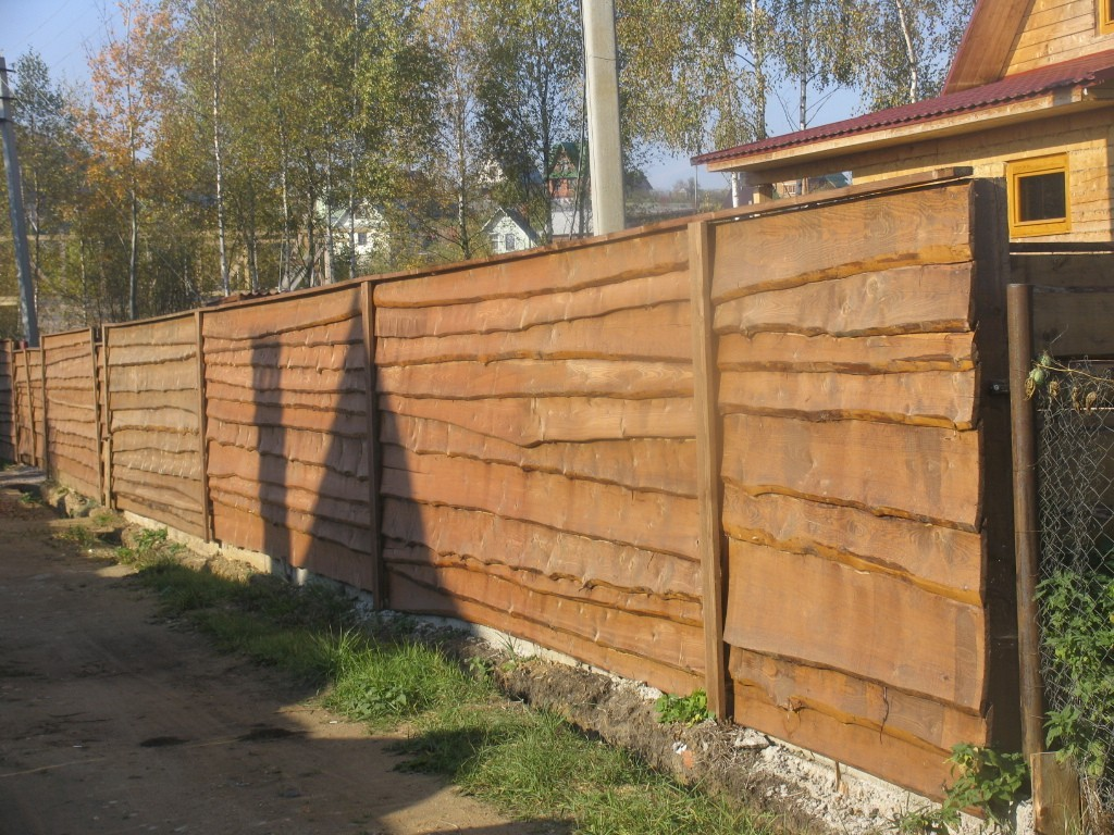 Глухой забор-лесенка из низкосортной древесины