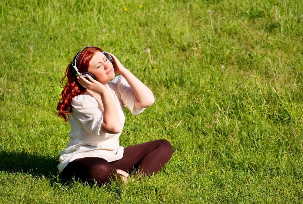 Девушка в наушниках на луговом газоне