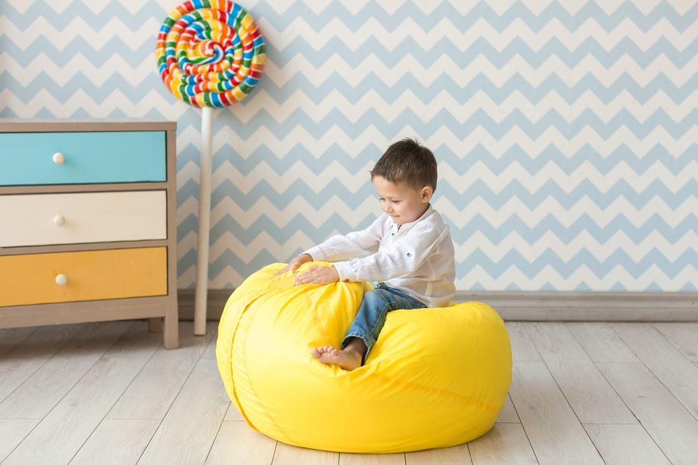 Малыш на желтом кресле-мешке в своей комнате