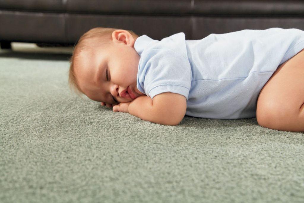 Спящий младенец на ковролине нейтрального цвета