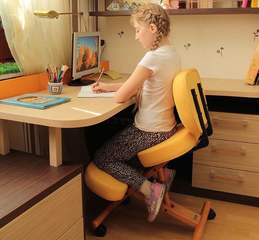 Девочка школьного возраста на ортопедическом стуле