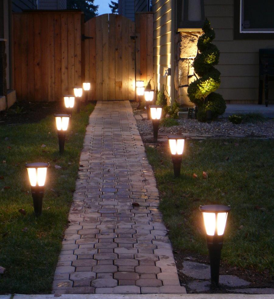 Садовые фонарики вдоль тропинки из брусчатки