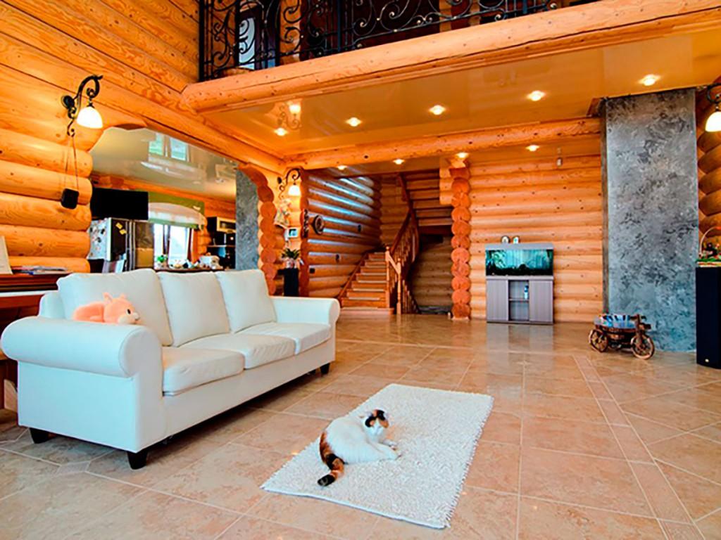 Белый диван в гостиной дома из бревен