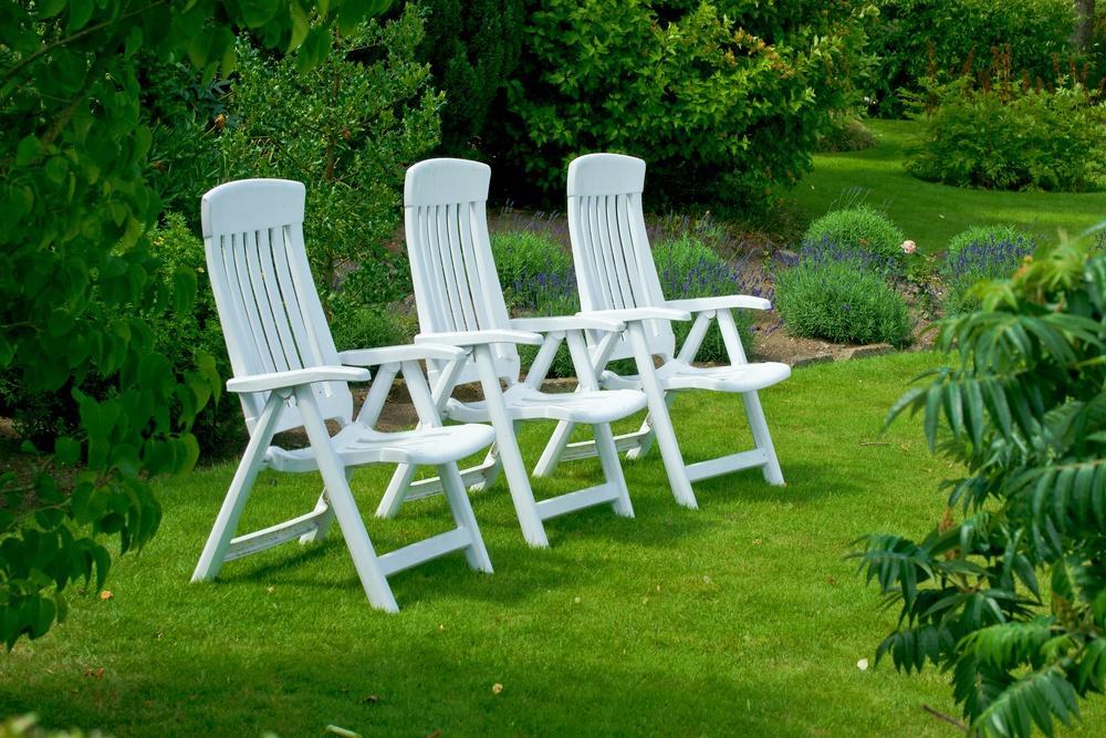 Белые садовые кресла на парковом газоне