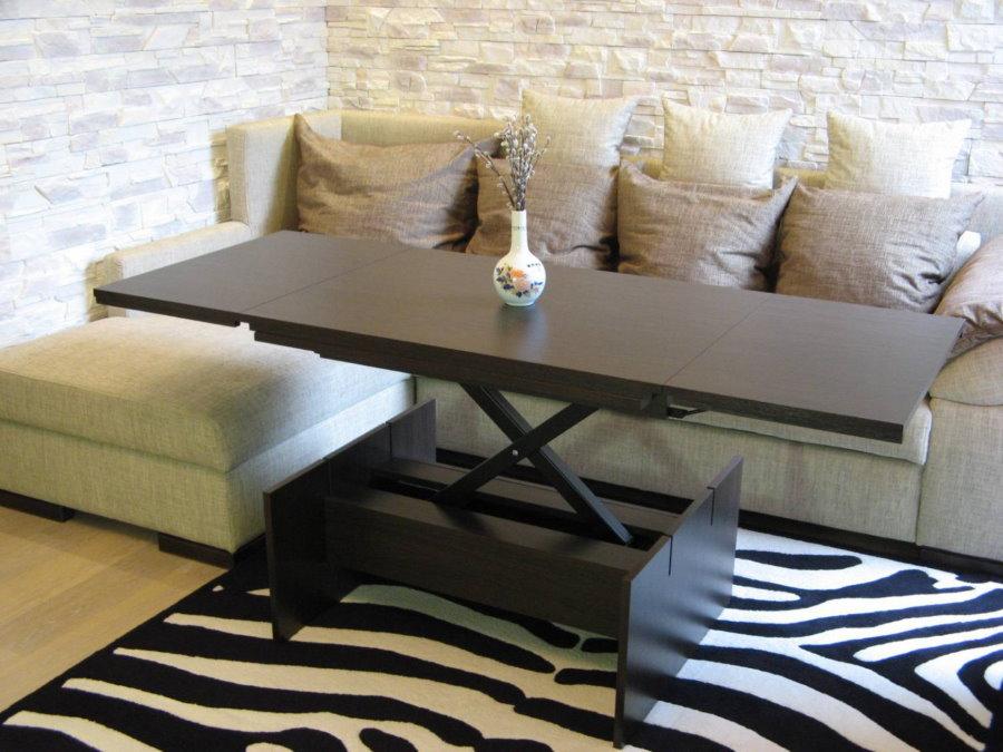 Раскладной стол перед угловым диваном в зале