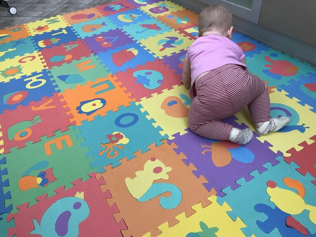 Маленький ребенок на мягком покрытии из цветных пазлов