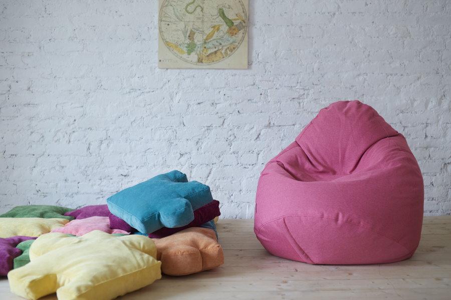 Розовое кресло-мешок на фоне кирпичной стены