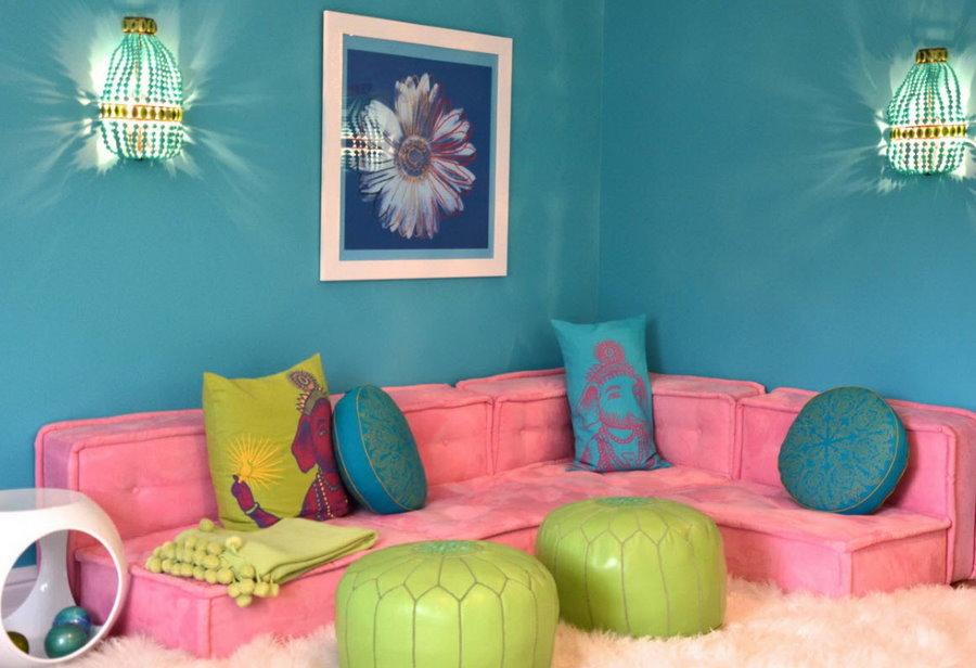 Розовый диванчик на фоне бирюзовой стены