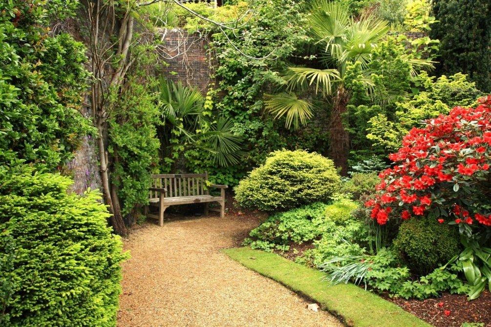 Деревянная лавочка под деревьями сада в пейзажном стиле