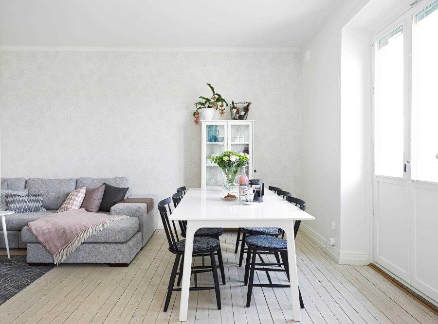 Серый диван в белой кухне-гостиной
