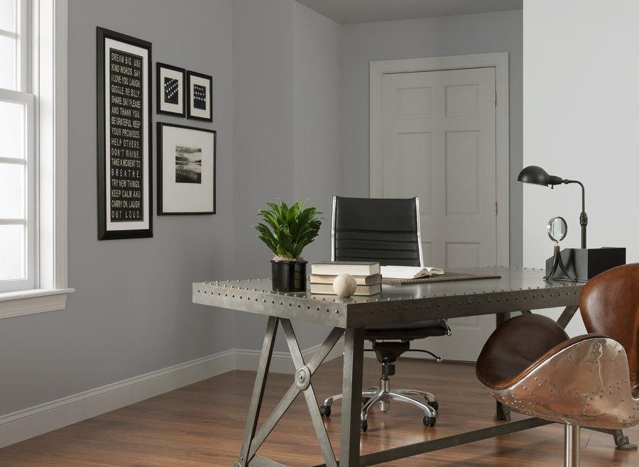 Металлический стол в домашнем кабинет с серыми стенами
