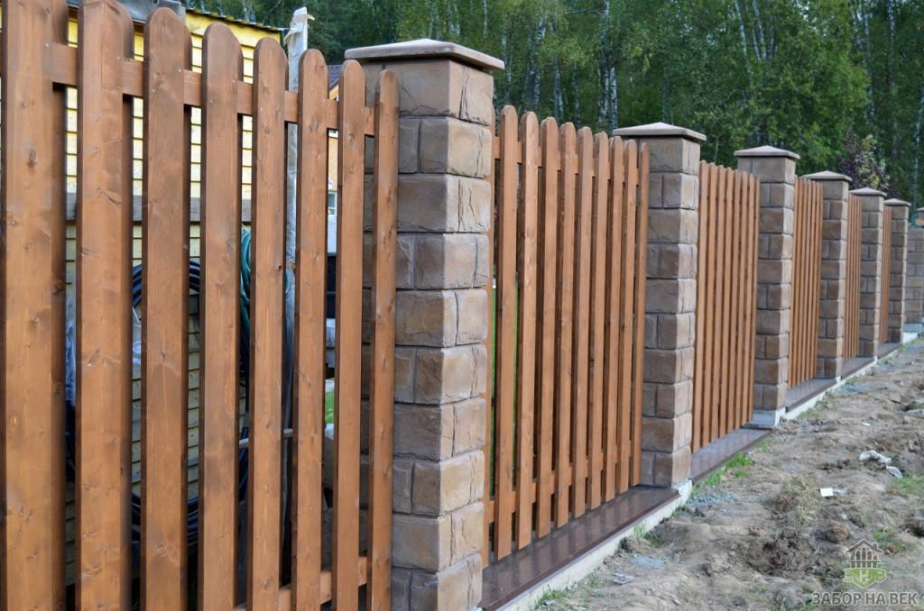 Деревянный забор с просветами на кирпичных столбах