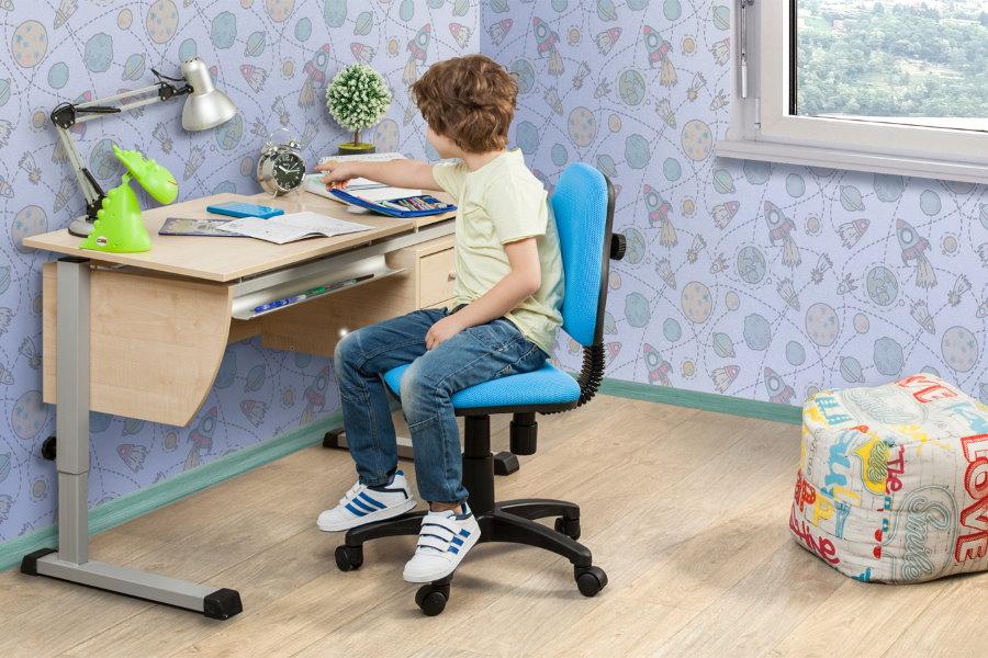 Школьник в своей комнате на стуле с колесиками