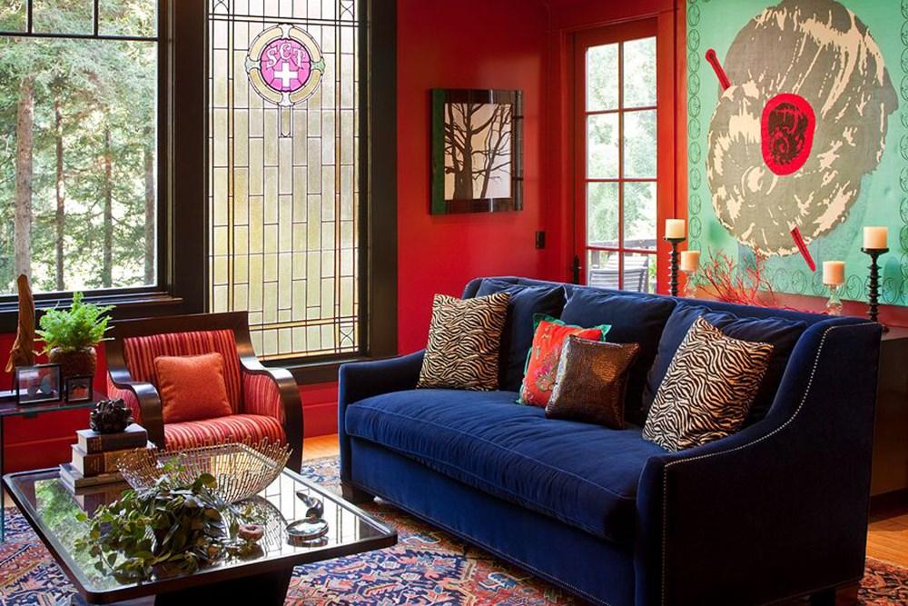 Синий диван в гостиной с красными стенами