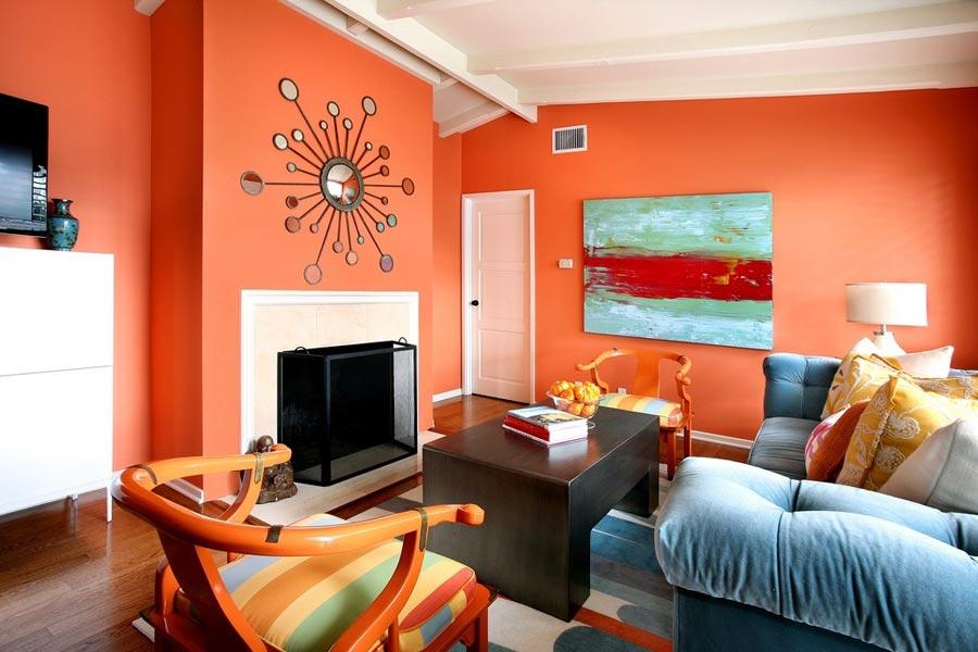 Яркая окраска стен в гостиной с синим диваном