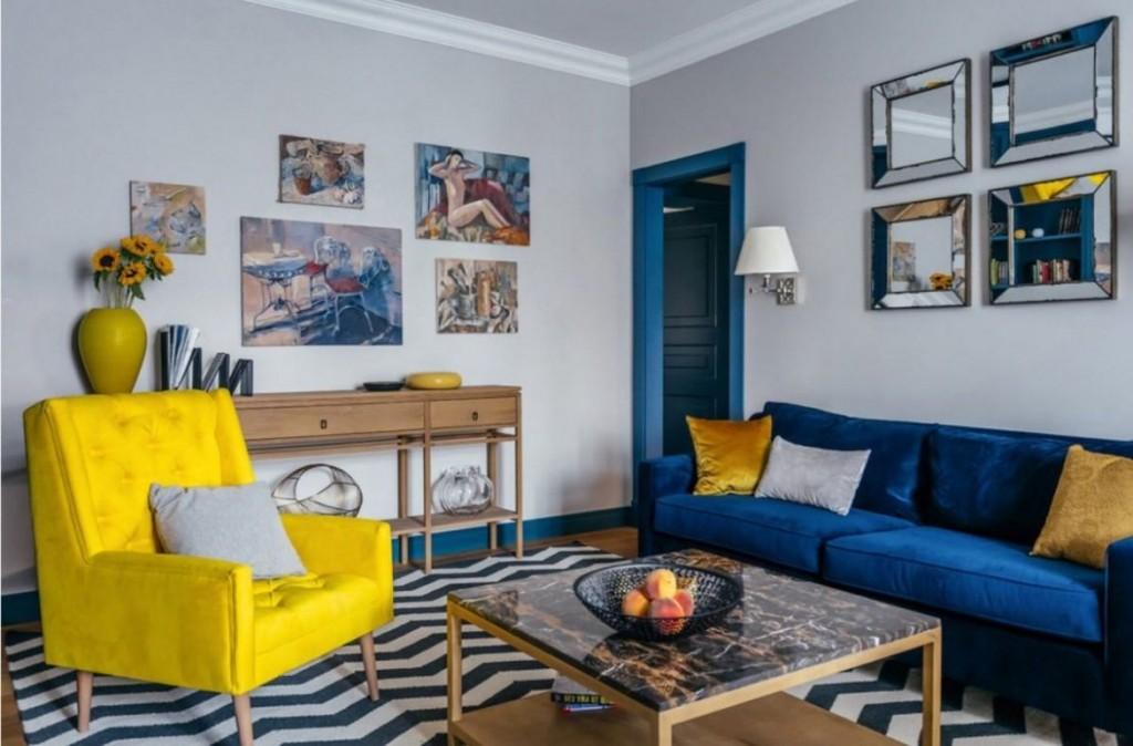 Синий диван в зале с желтым креслом