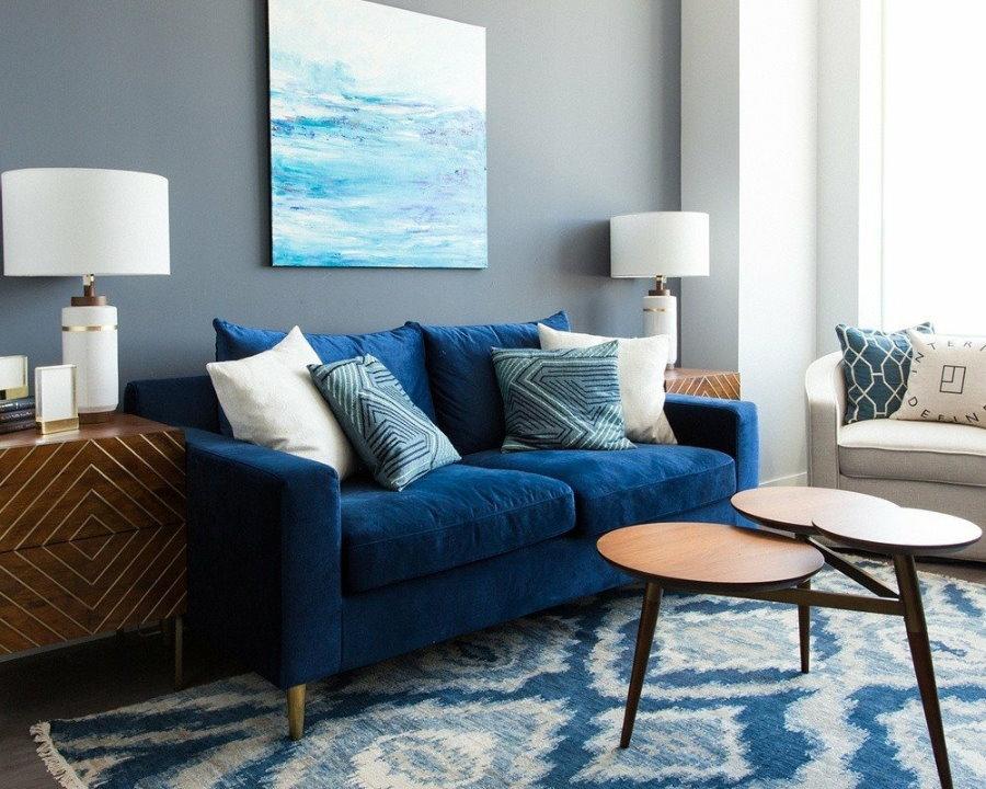Декорирование стены в гостиной над синем диваном
