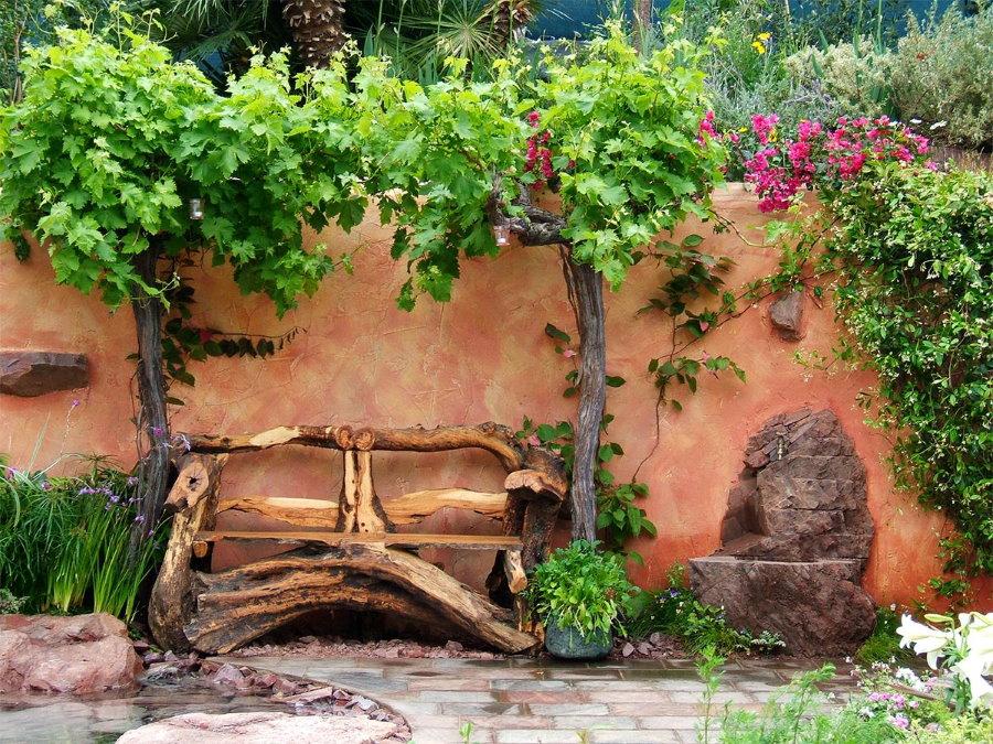 Самодельная скамейка из дерева возле стены сарая