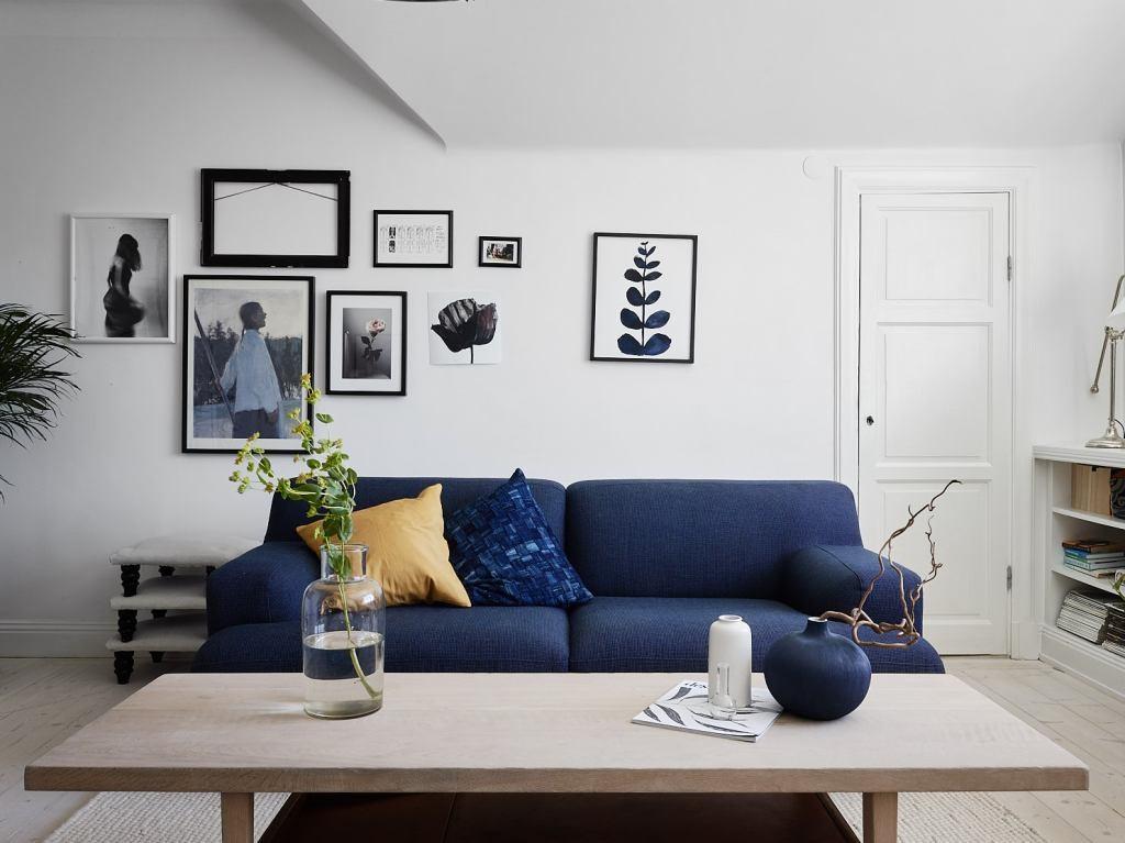 Синий диван на фоне белых стен гостиной