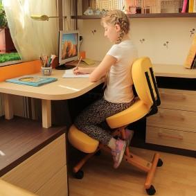 Девочка на ортопедическом коленном стуле