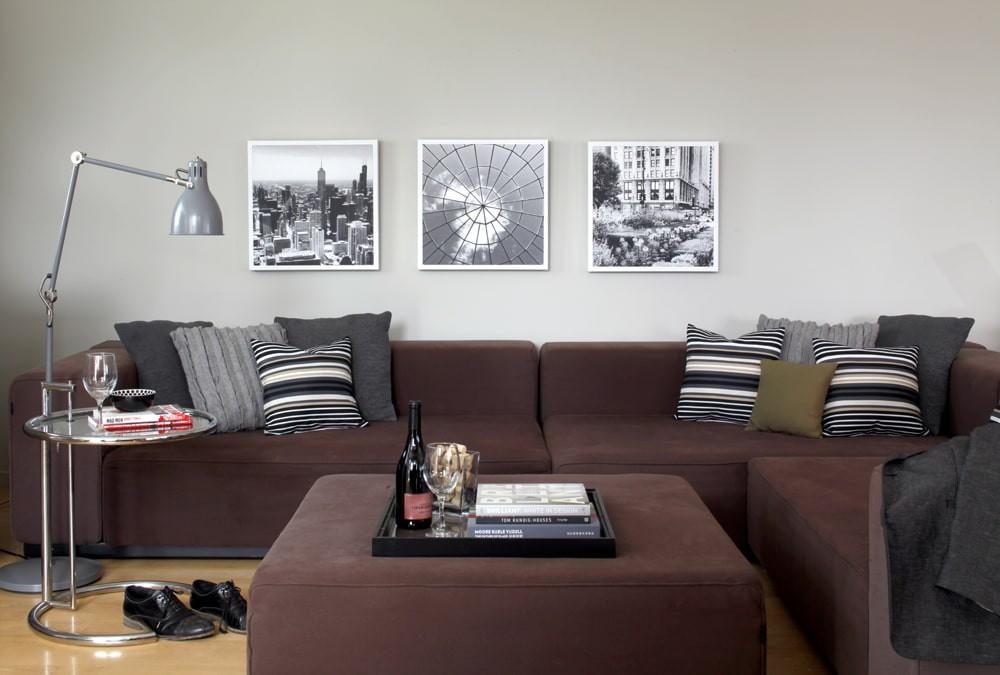 Три фотографии в тонких рамках над диваном