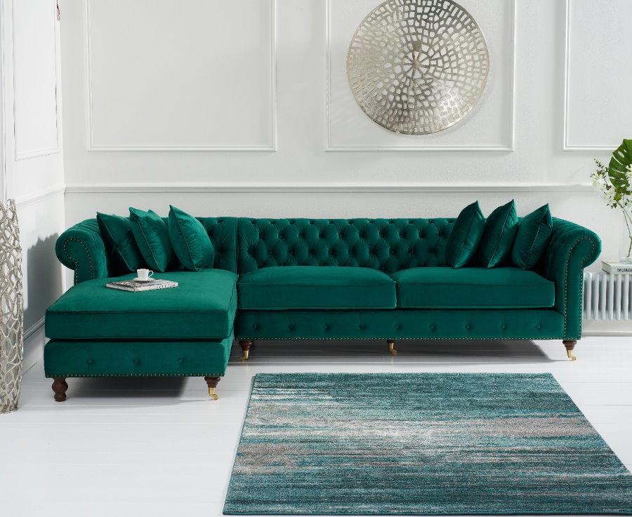 Изумрудный диван углового типа в белом зале