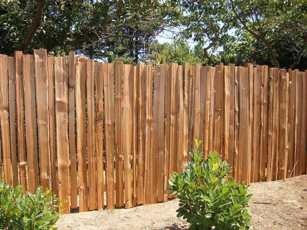 Деревянная ограда из горбыля на дачном участке