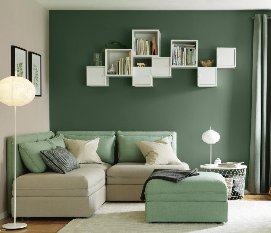 Белые полки на зеленой стене гостиной