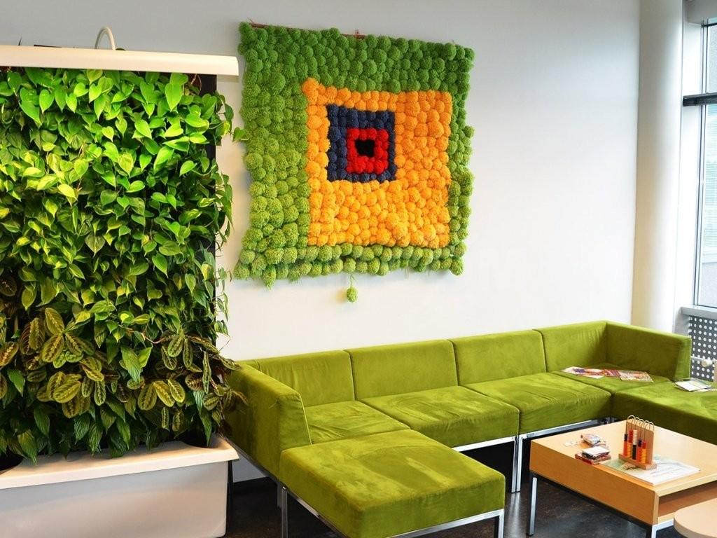 Живая стена в комнате с зеленым диваном