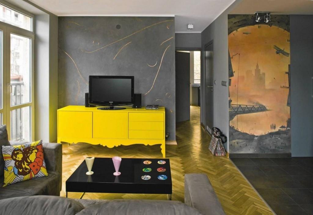 Желтая тумба на фоне серой стены гостиной