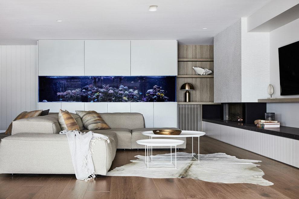 Длинный аквариум в интерьере светлой гостиной