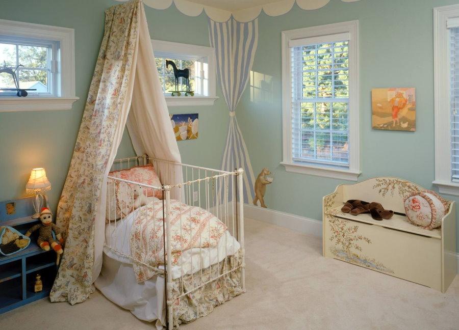 Кроватка ребенка с балдахином из пестрой ткани